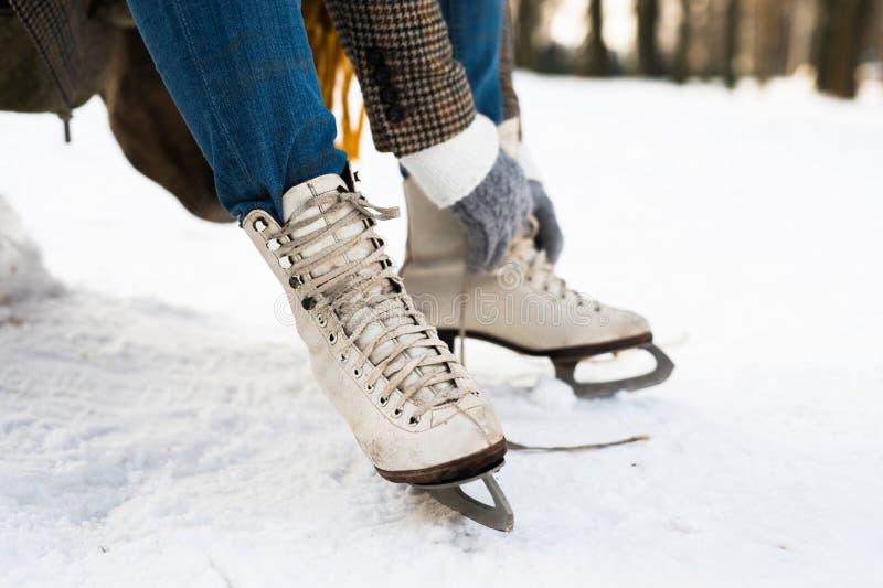 A mulher irreconhecível no inverno veste a colocação sobre patins de gelo velhos foto de stock