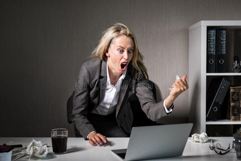 Mulher irritada em seu laptop no trabalho imagem de stock
