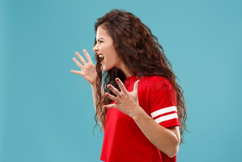 A mulher irritada emocional nova que grita no fundo azul do estúdio imagem de stock royalty free