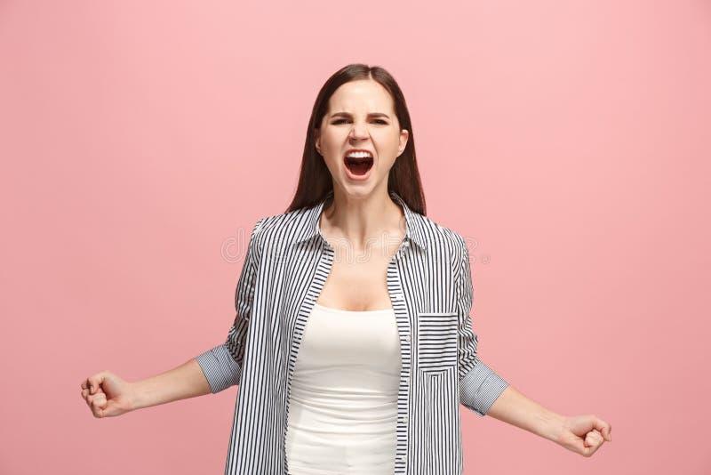 A mulher irritada emocional nova que grita no fundo cor-de-rosa do estúdio fotos de stock