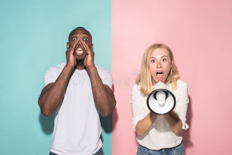 A mulher irritada emocional nova que grita no fundo cor-de-rosa do estúdio fotografia de stock royalty free