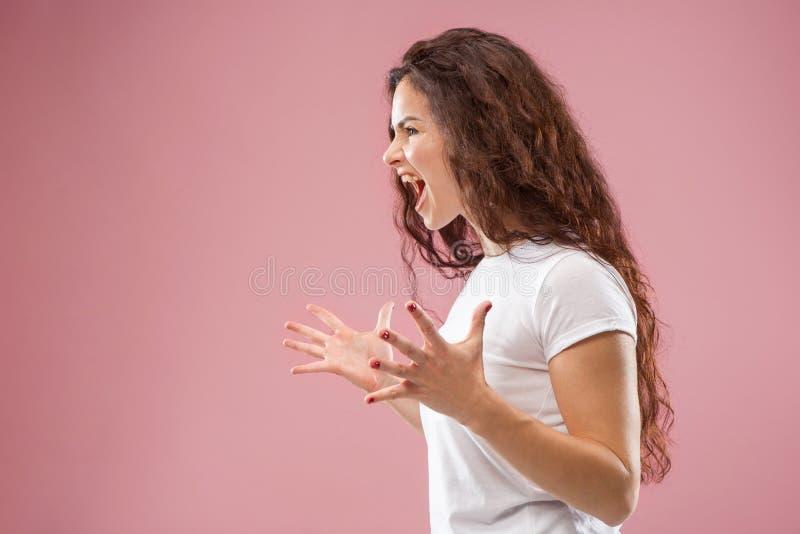 A mulher irritada emocional nova que grita no fundo cor-de-rosa do estúdio fotografia de stock
