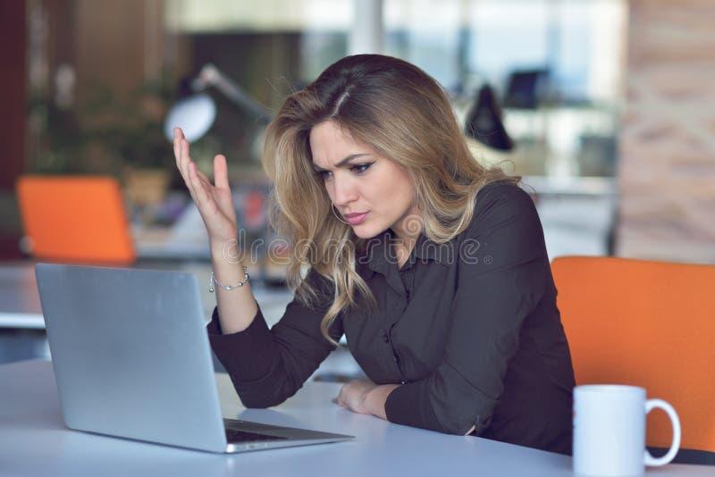 Mulher irritada frustrante que grita em seu portátil fotografia de stock