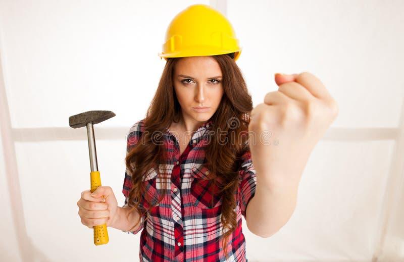 A mulher irritada guarda o martelo e mostra o punho fotografia de stock royalty free