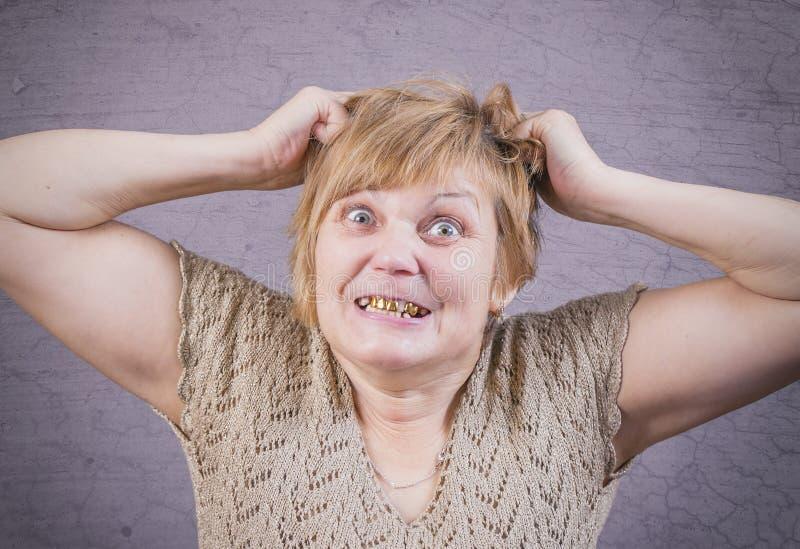 Mulher irritada muito emocional com dentes do ouro em um fundo cinzento foto de stock