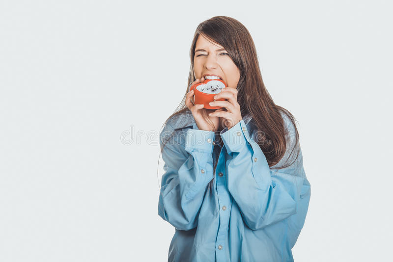 Mulher irritada na camisa grande que guarda o despertador fotos de stock