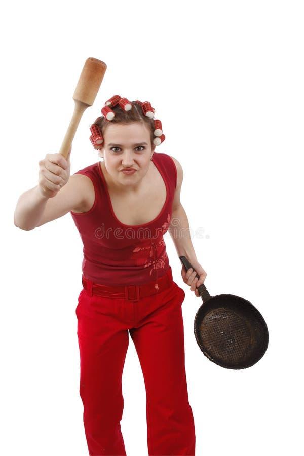 Mulher irritada nos rolos do cabelo, prendendo uma frigideira. fotografia de stock