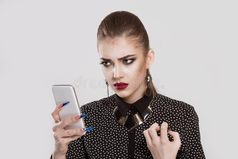 Mulher irritada, olhando curiosamente no telefone, não gosta do que vê imagens de stock
