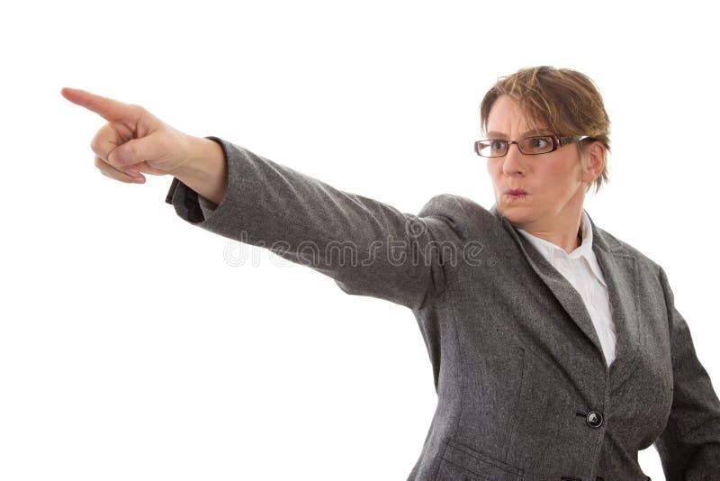 Mulher irritada que aponta afastado - a mulher isolada no fundo branco imagens de stock royalty free