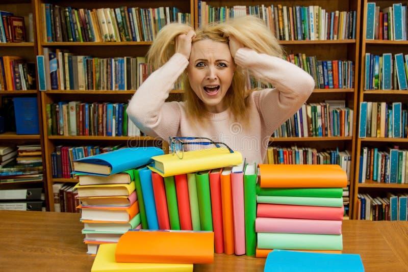 Mulher irritada que grita, menina caucasiano com o cabelo longo, gritando com fúria na biblioteca imagens de stock