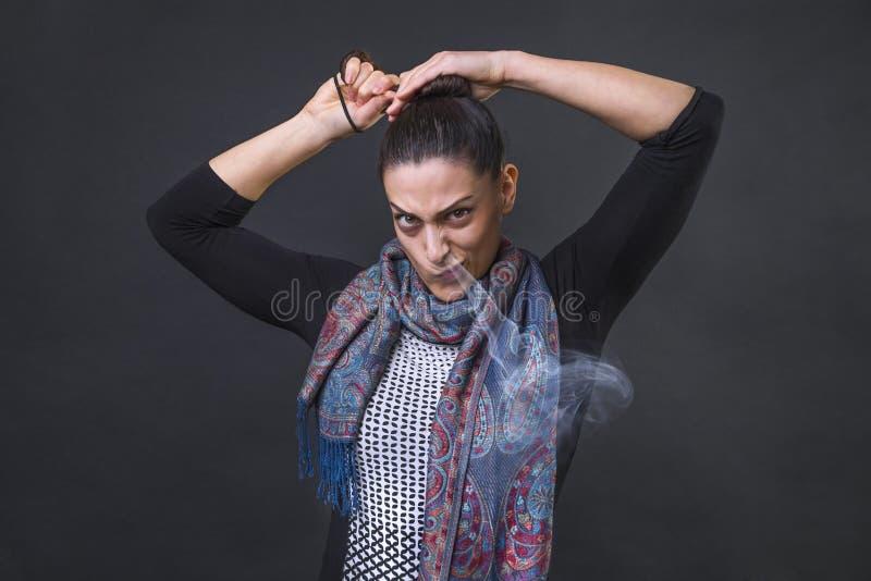 Mulher irritada que grita na frustração, incapaz furioso de amarrar sua cauda de pônei e cozinhando fora de seu nariz foto de stock