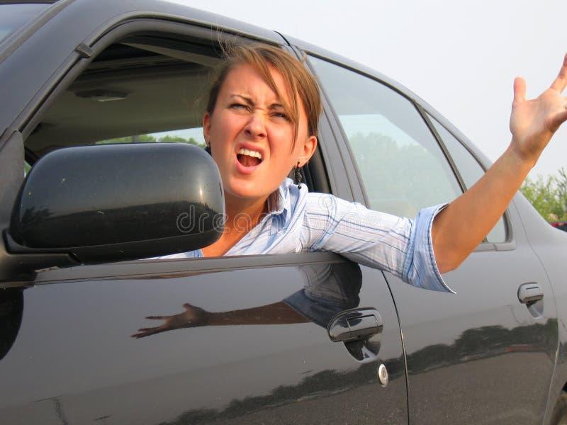 Mulher irritada que grita para fora o indicador de carro fotografia de stock