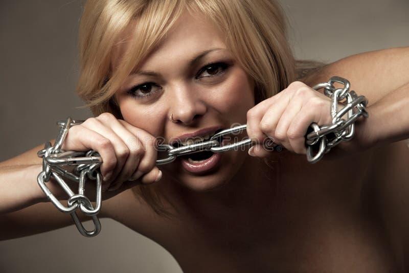 Mulher irritada que morde uma corrente do cromo fotos de stock royalty free