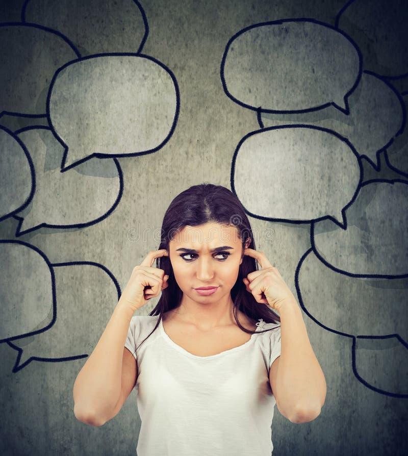 Mulher irritada que obstrui suas orelhas cansados de demasiada conversa fotos de stock royalty free