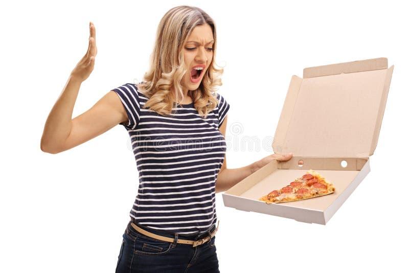 Mulher irritada que olha uma caixa da pizza imagem de stock