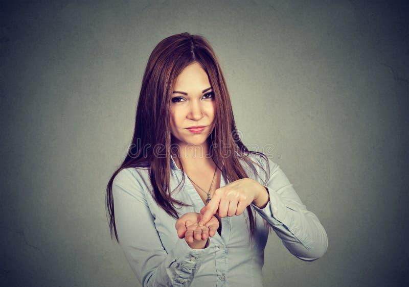 A mulher irritada que pede mais dinheiro, paga para trás o débito fotografia de stock
