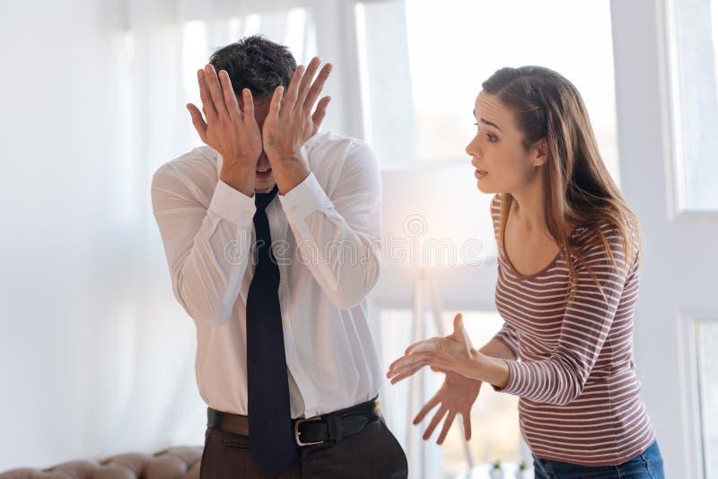 Mulher irritada que responsabiliza seu marido irritado cansado durante sua discussão imagens de stock