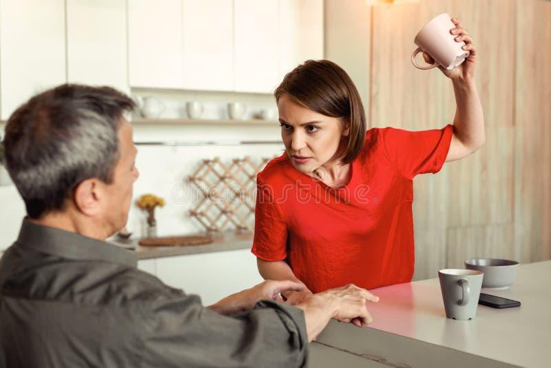Mulher irritada resoluto no t-shirt vermelho que joga o copo vazio fotos de stock royalty free