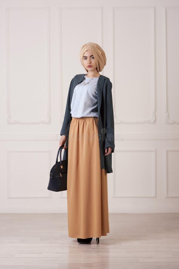Mulher islâmica bonita nova na roupa oriental moderna com bolsa imagem de stock royalty free