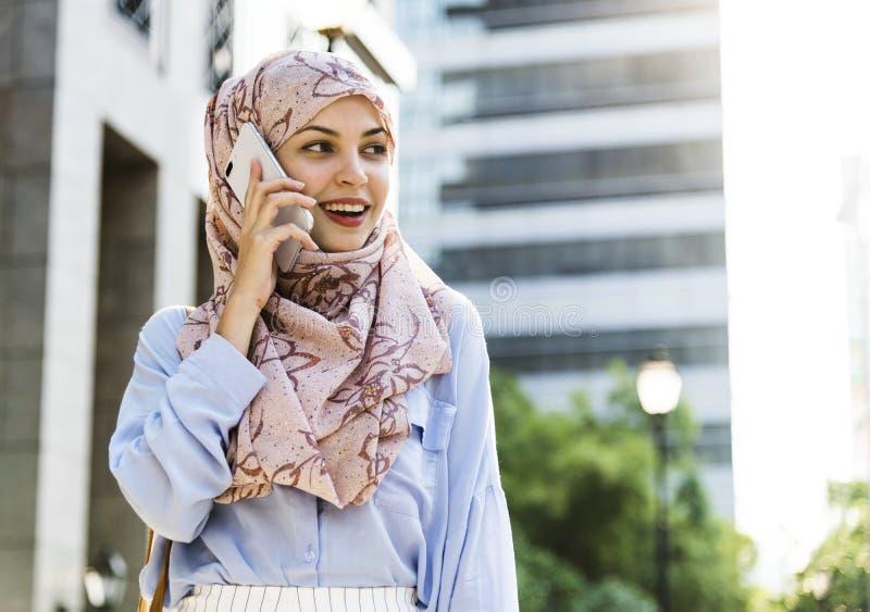 Mulher islâmica que usa o telefone celular com sorriso na construção imagens de stock