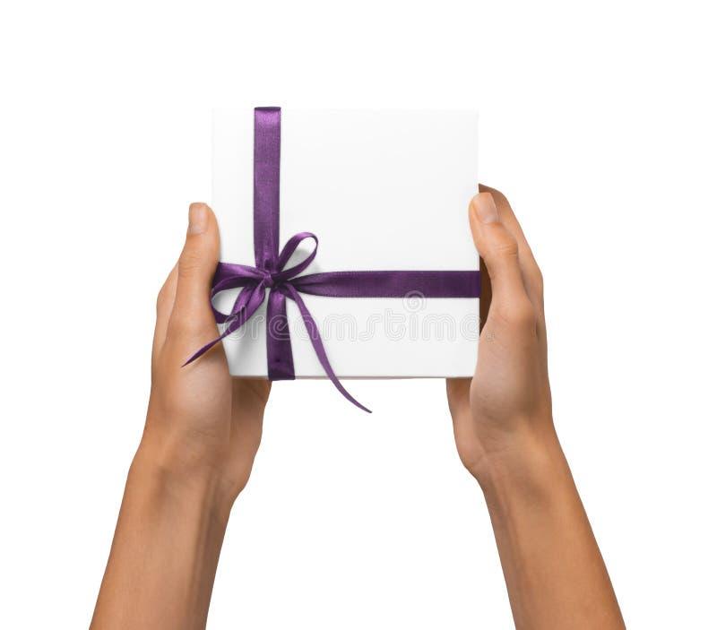 A mulher isolada entrega guardar a caixa branca atual do feriado com fita roxa em um fundo branco fotos de stock royalty free