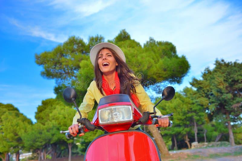 Mulher italiana bonita nova que senta-se em um 'trotinette' italiano em montes de Itália foto de stock