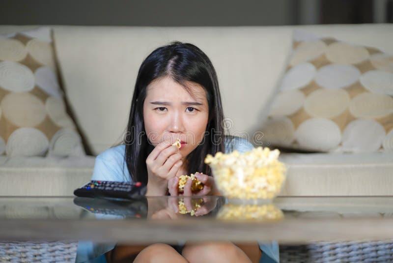 Mulher japonesa asiática bonita e relaxado nova que olha o drama coreano na televisão no filme romântico triste que come a pipoca imagem de stock
