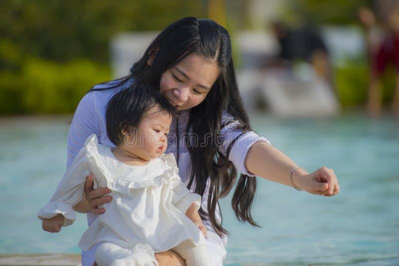 Mulher japonesa asiática feliz e bonito nova que joga com o bebê da filha na apreciação tropical da piscina do recurso dos feriad imagem de stock royalty free