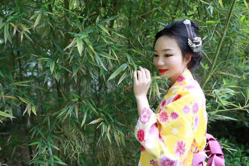 Mulher japonesa asiática tradicional com suporte de sorriso da noiva japonesa do quimono pelo bambu em um parque da mola foto de stock royalty free