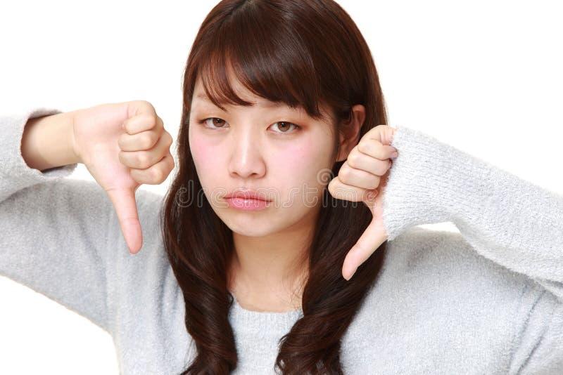 A mulher japonesa nova com polegares gesticula para baixo fotos de stock