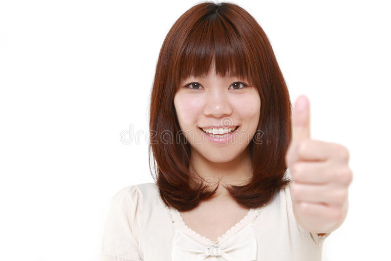 A mulher japonesa nova com polegares levanta o gesto foto de stock