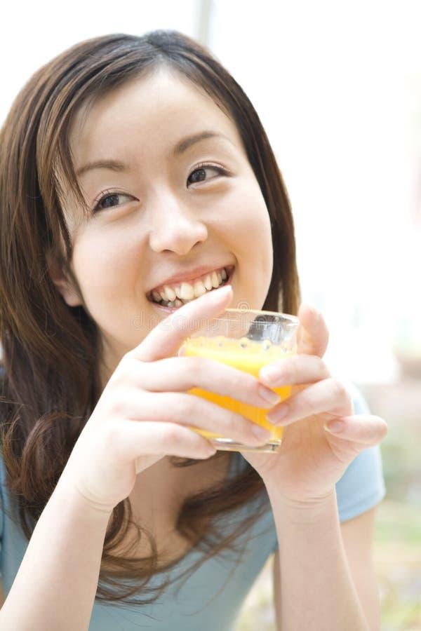 Mulher japonesa que bebe um sumo de laranja fotografia de stock