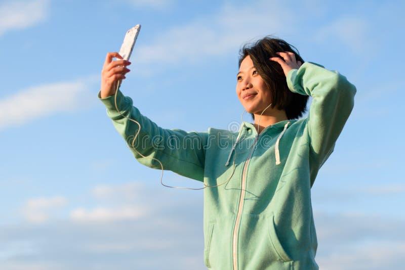 Mulher japonesa sensual com o cabelo curto que toma o selfie exterior usando seu telefone Fundo azul do céu nebuloso imagem de stock royalty free