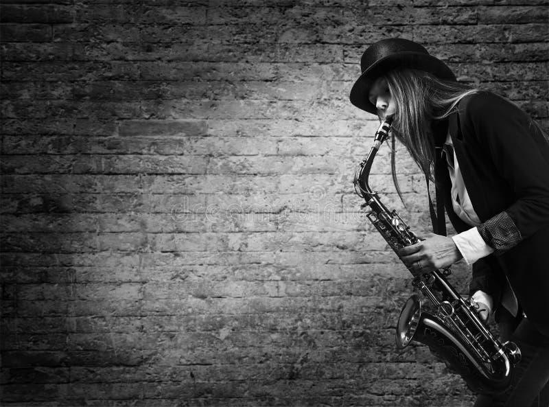 A mulher joga o saxofone na perspectiva de um tijolo velho imagem de stock