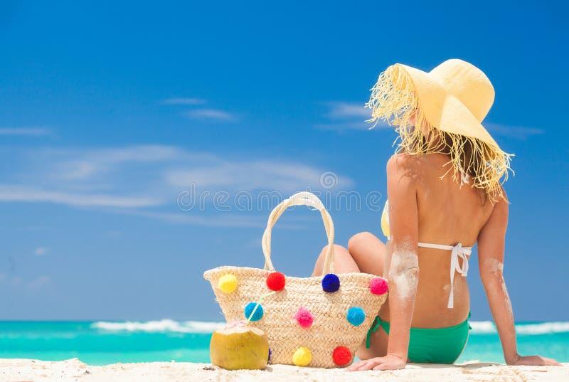 Mulher jovem de biquíni e chapéu de palha e com saco de palha colorido relaxando na praia branca de caribbean foto de stock