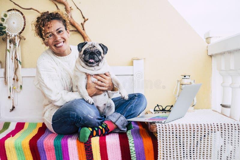 Mulher jovem e cachorro animados em casa em abraço ao ar livre e se divirtam e amam juntos - laptop na mesa para fotos de stock