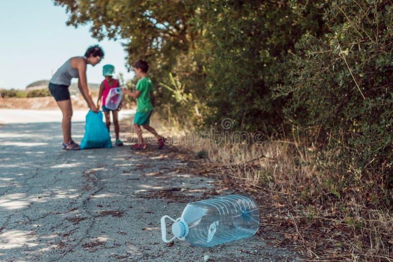 Mulher jovem ensinando seus filhos a serem ambientalmente responsáveis enquanto pega lixo no campo fotos de stock