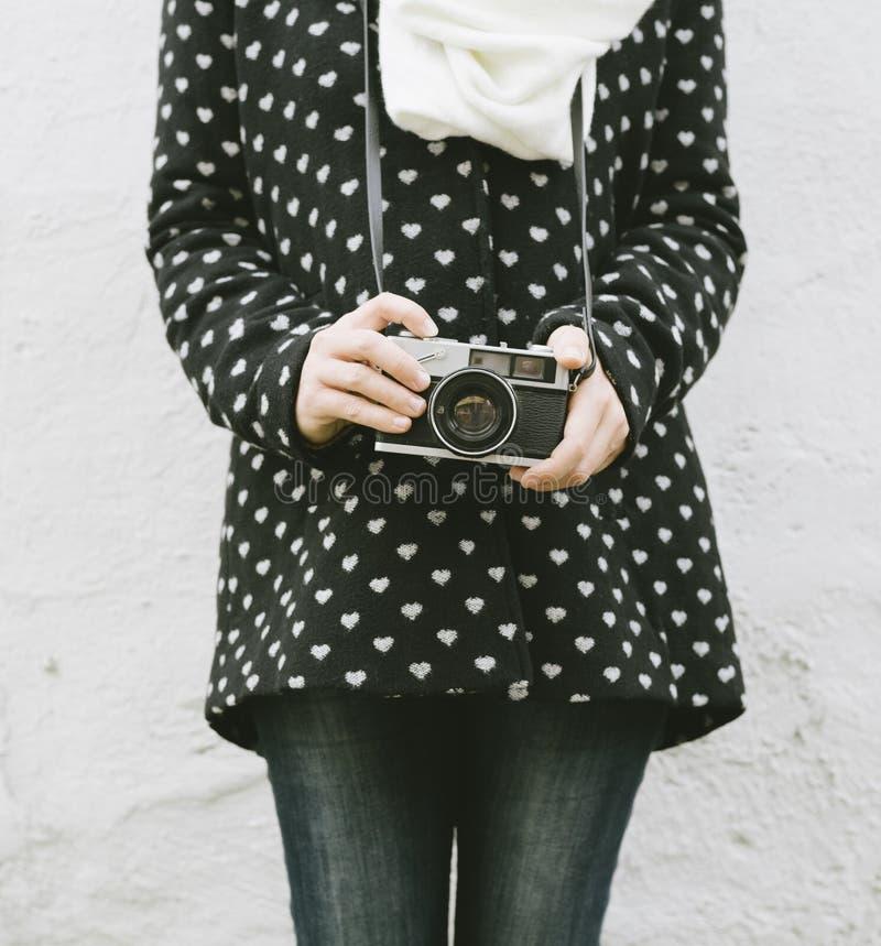 Mulher jovem hipster segurando câmera fotográfica vintage imagem de stock royalty free