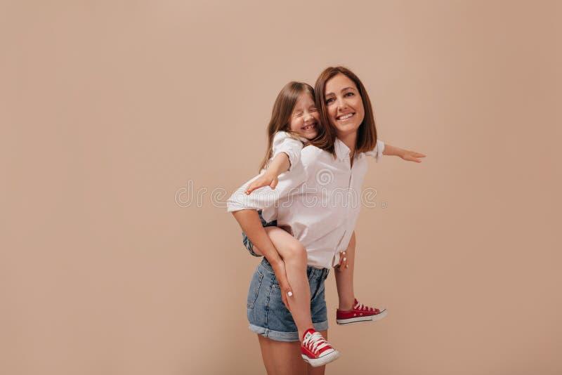 Mulher jovem inspirada sem maquiagem passando tempo com a filha, carregando seu piggyback sobre um fundo isolado foto de stock