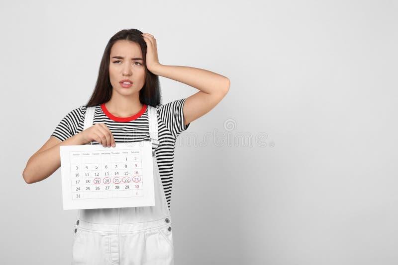 Mulher jovem que mantém um calendário com dias de ciclo menstrual marcados sobre fundo leve Espaço para texto fotografia de stock royalty free