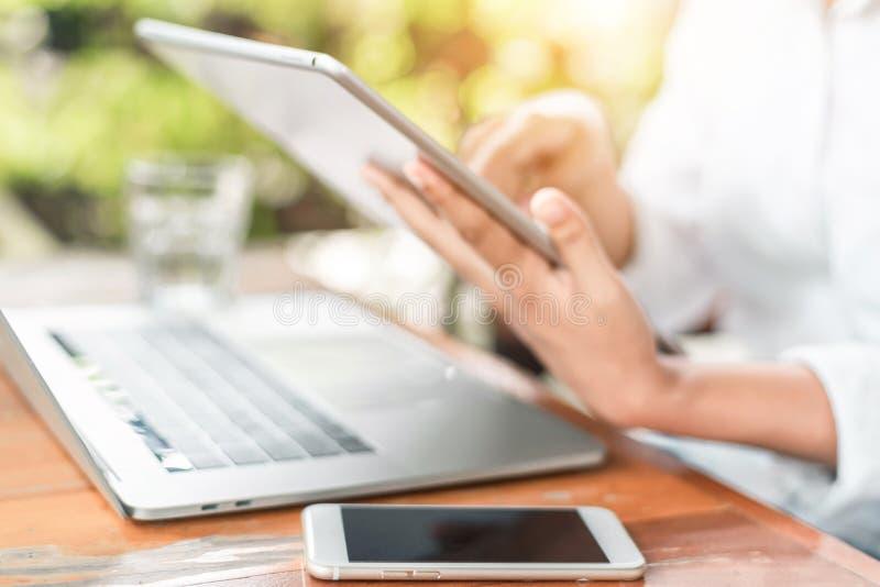 Mulher jovem sentada na cafeteria à mesa de madeira, tomando café e usando smartphone Na mesa está o laptop Navegação infantil fotos de stock royalty free