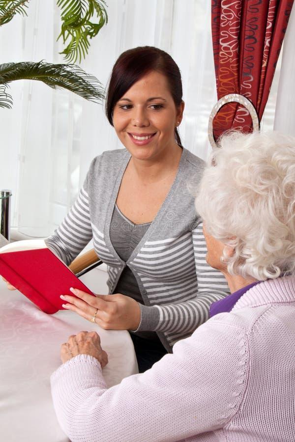 A mulher lê aos séniores de um livro. foto de stock royalty free