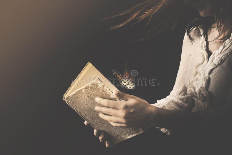 A mulher lê um livro aonde as borboletas saiam imagem de stock