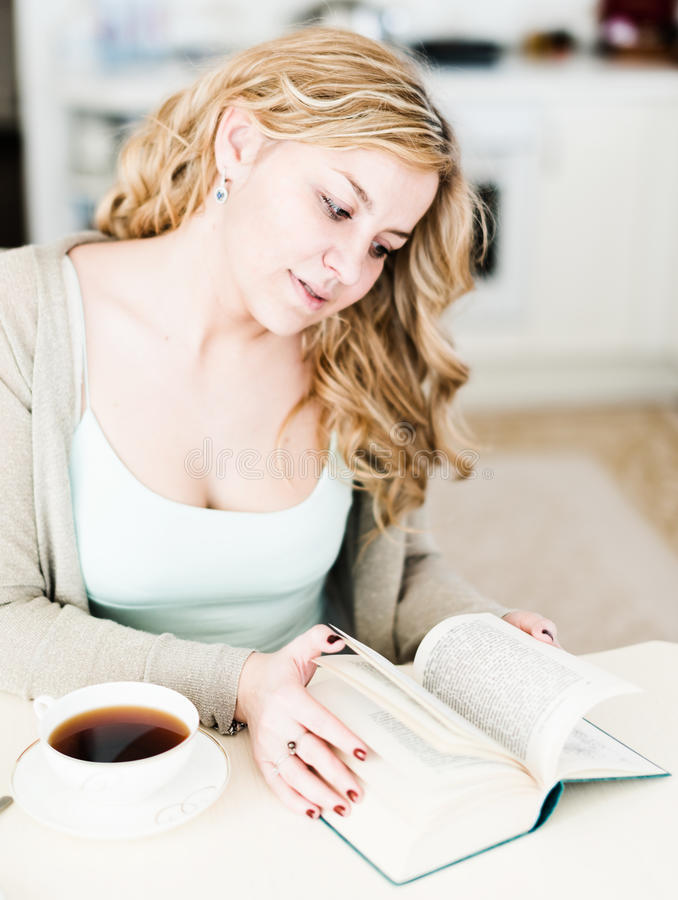 A mulher lê um livro interessante e bebe o café fotografia de stock