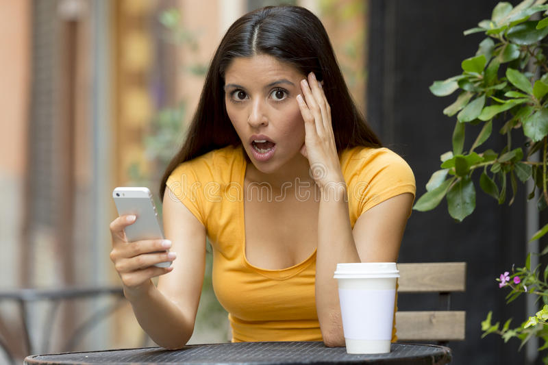 Mulher latin atrativa chocada em seu telefone esperto imagens de stock royalty free
