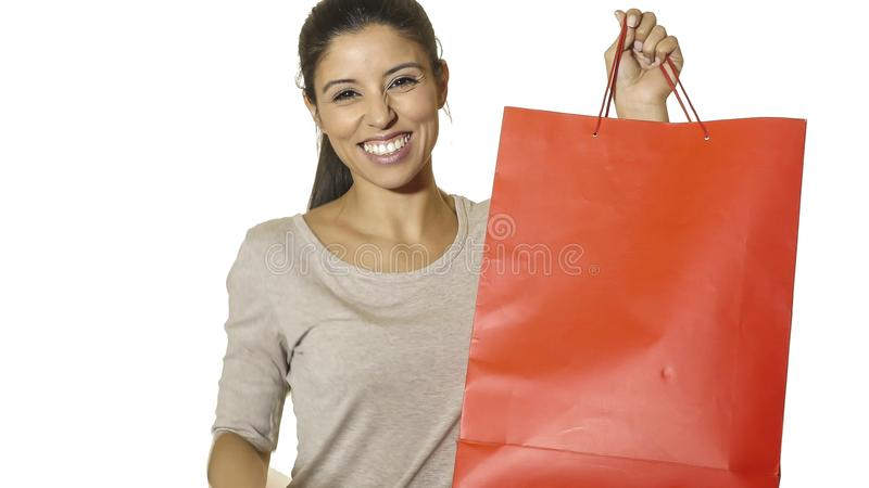 Mulher latin atrativa e feliz nova que mantêm o sorriso vermelho do saco de compras alegre e positivo isolado no fundo branco na  imagens de stock royalty free
