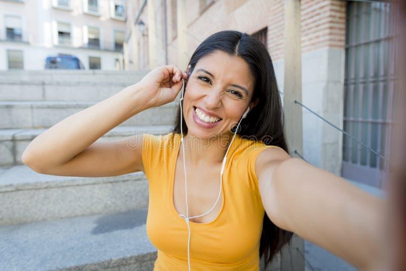 Mulher latin atrativa que escuta a música em seu telefone esperto foto de stock