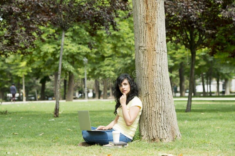 Mulher latin atrativa que trabalha e que studing em seu latop em um parque verde fotos de stock