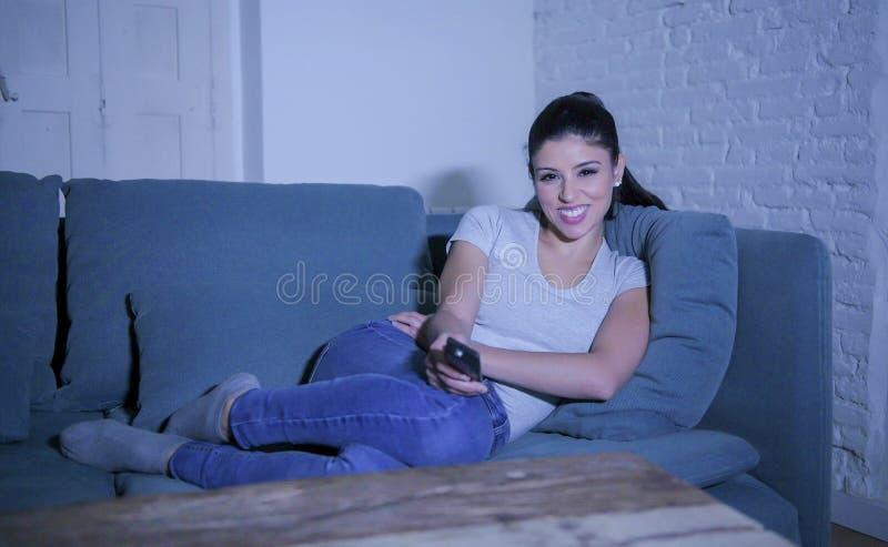 mulher latin bonita e feliz nova em seu 30s que guarda o telecontrole da tevê que aprecia em casa o programa televisivo de observ imagem de stock royalty free