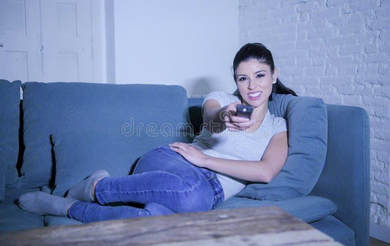 mulher latin bonita e feliz nova em seu 30s que guarda o telecontrole da tevê que aprecia em casa o programa televisivo de observ fotografia de stock royalty free